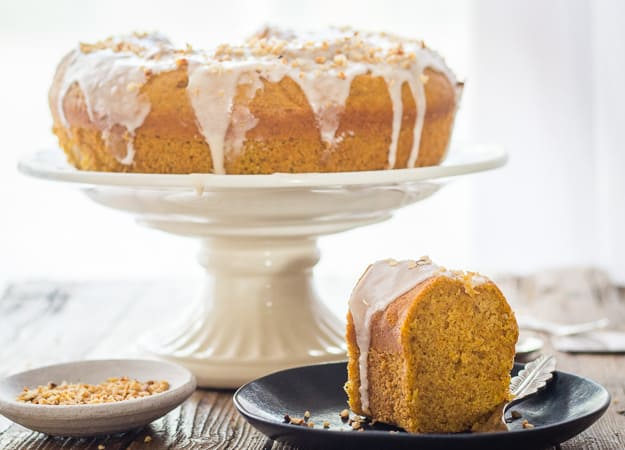 maple glazed pumpkin cinnamon cake on a cake stand with a piece on a plate