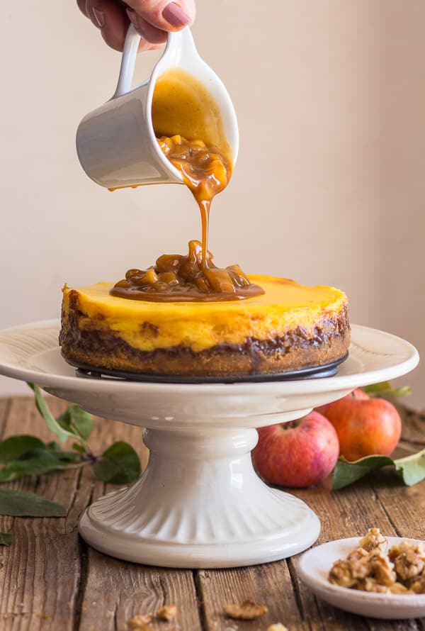 pouring maple caramel sauce from a small white jug onto the finished apple cheesecake.