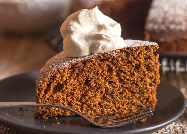 an up close of a slice of gingerbread cake on a plate with a fork