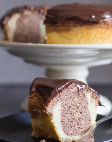 marble cake on a cake stand a slice on a black plate