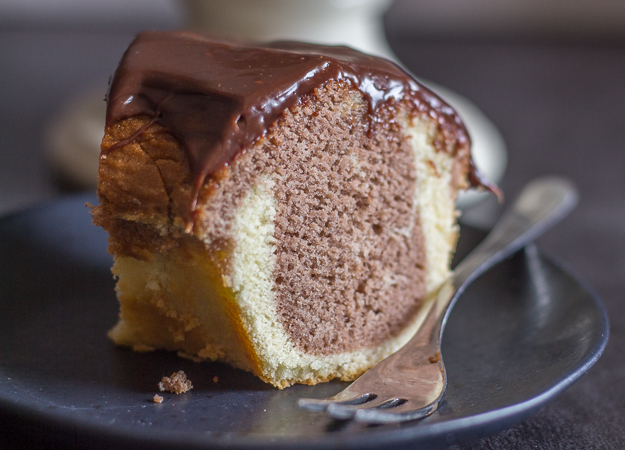 up close photo of a slice of marble cake on a black plate with a fork