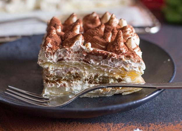 up close puff pastry tiramisu on a black plate.