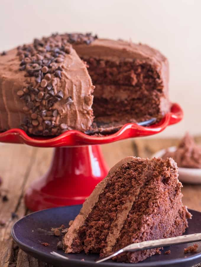 chocolate cake with mocha icing on a red cake stand with a slice on a black plate