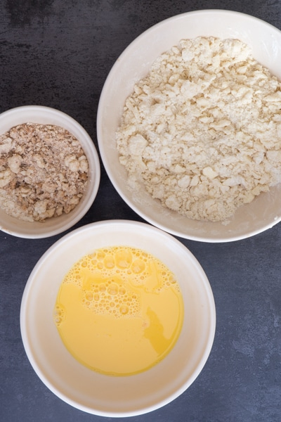 The whisked dried ingredients in a bowl, the egg, sugar and vanilla beaten in a white bowl and the streusel in a bowl