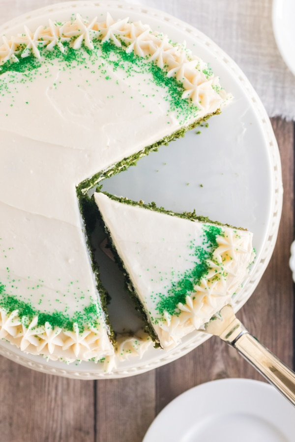 green velvet cake on a white cake stand with a piece sliced