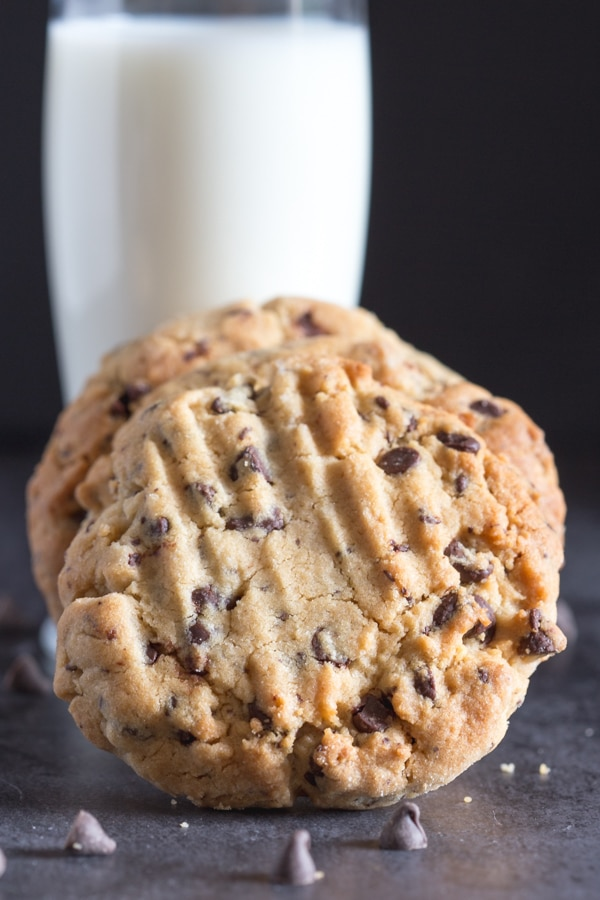 2 peanut butter cookies leaning against a glass of milk