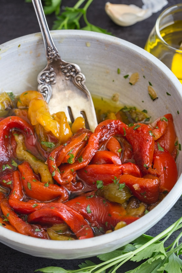 a fork in the white bowl with roasted peppers