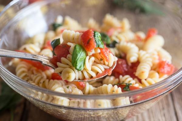 fresh tomato pasta salad in a glass bowl