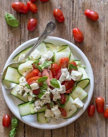 zucchini caprese salad on a white plate