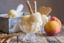 fresh peach ice cream in a bowl with fresh peaches