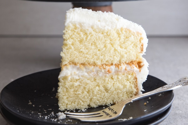 coconut cake slice on a black plate