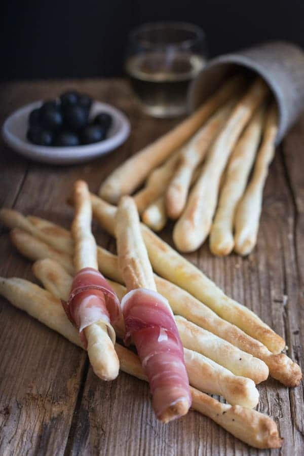 breadsticks on a board with two wrapped with prosciutto