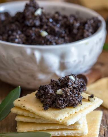 black olive tapenade in a bowl and on a cracker