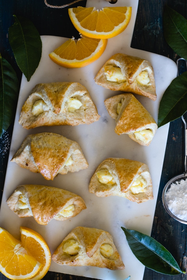 orange cream cheese filled baked croissant on a white board