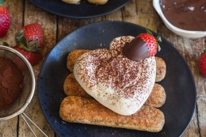 up close classic tiramisu heart shaped with a chocolate dipped strawberry