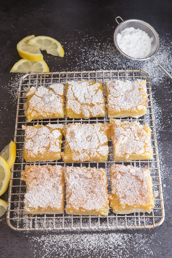 lemon squares cut on a wire rack dusted with powdered sugar