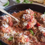 baked meatballs in a pan with one on a spoon