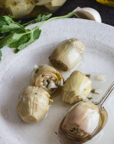 artichokes under oil on a white plate
