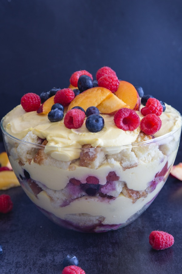 berry trifle in a glass bowl with fresh fruit on top