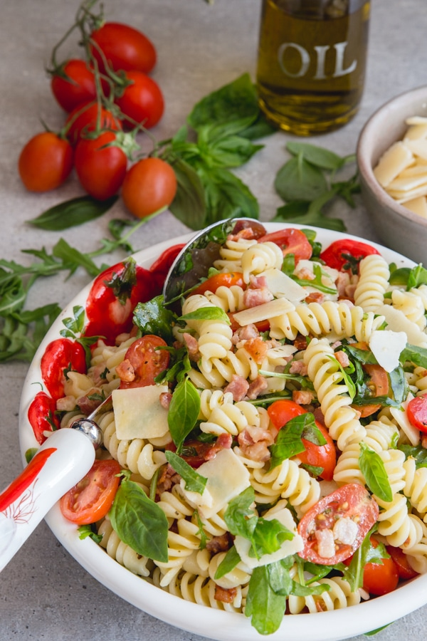 pasta salad in a bowl with tomatoes and oil on the side