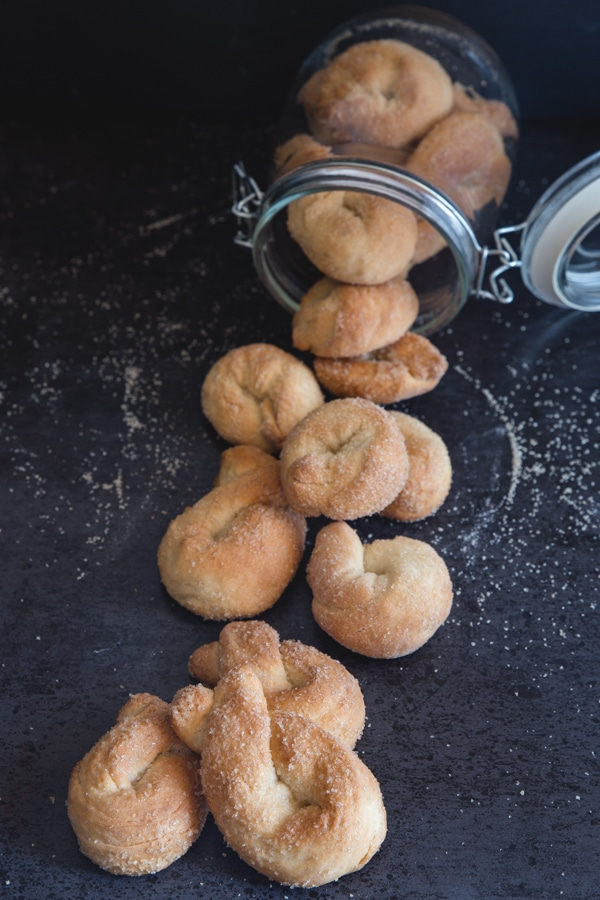 Italian twist cookies falling out of a glass jar