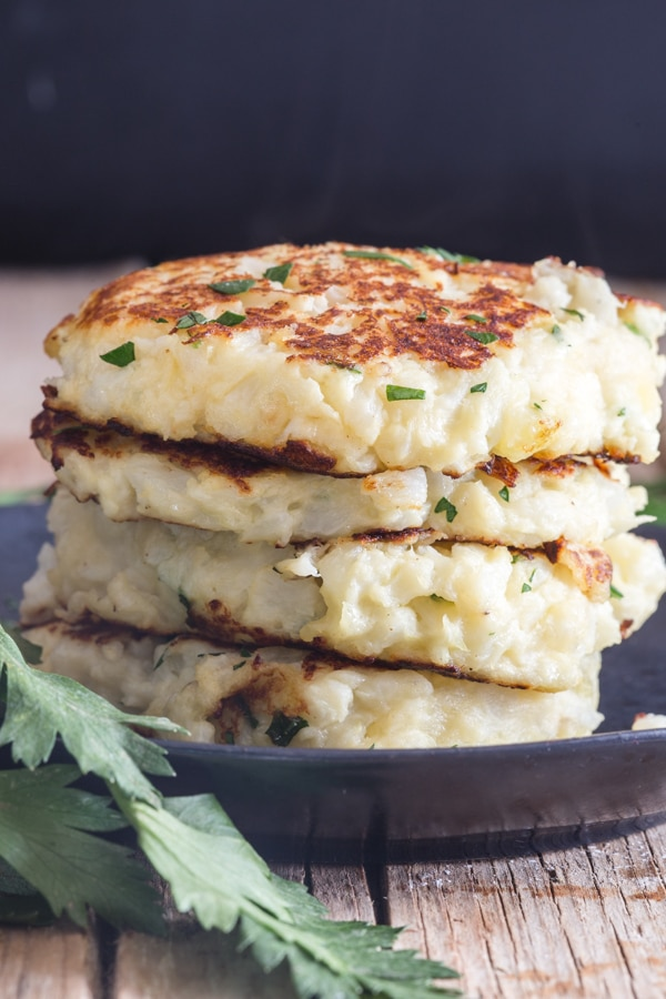 cauliflower fritters on a black plate with parsley