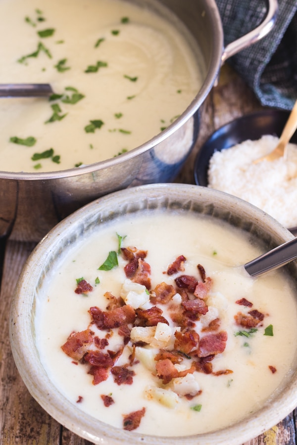 cauliflower soup in a silver pot with a ladle and in a bowl with chopped bacon and parmesan cheese in a small black bowl