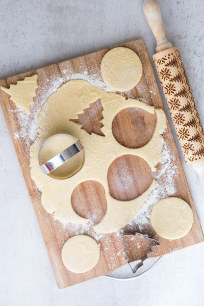 cutting out the cookie dough with cookie cutters on a wooden board