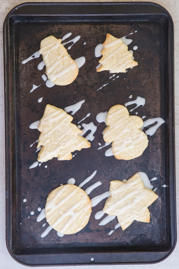 sugar cookies baked drizzled with lemon glaze on a black cookie sheet