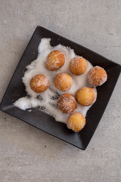 castagnole fried and rolling in sugar on a black plate