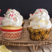 lemon cupcakes on a gold wire rack with one on a small cake stand