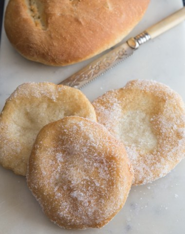 frittelle and bread on a white board with a knife