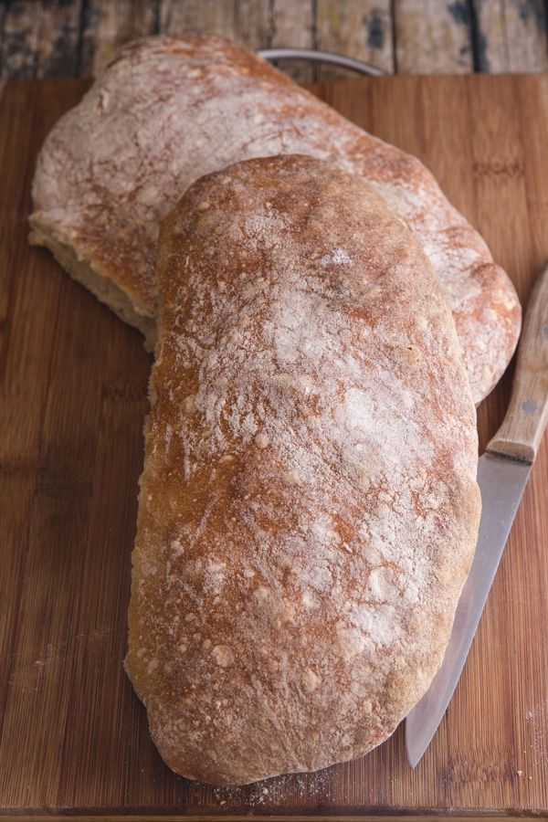 2 ciabatta loaves on a wooden board with a knife