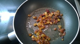 Raisins being sautéed in olive oil, till they are plump