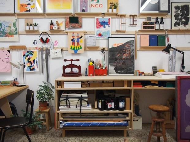 Vista da Lavandaria, com uma parede cheia de quadros e mesa com materiais de impressão.