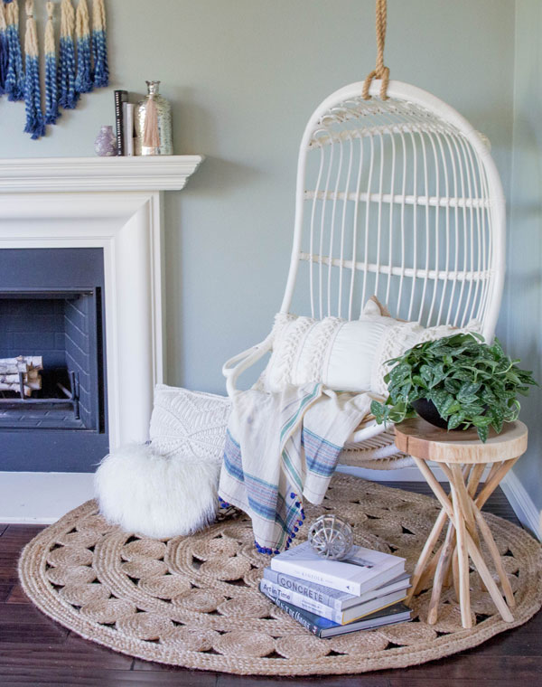 A beautiful hanging chair with comfy pillow and blankets.