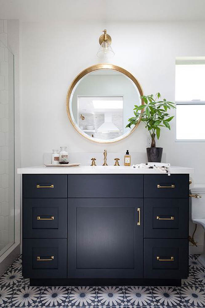 budget bathroom makeover cement tile floor brass fixtures navy cabinets