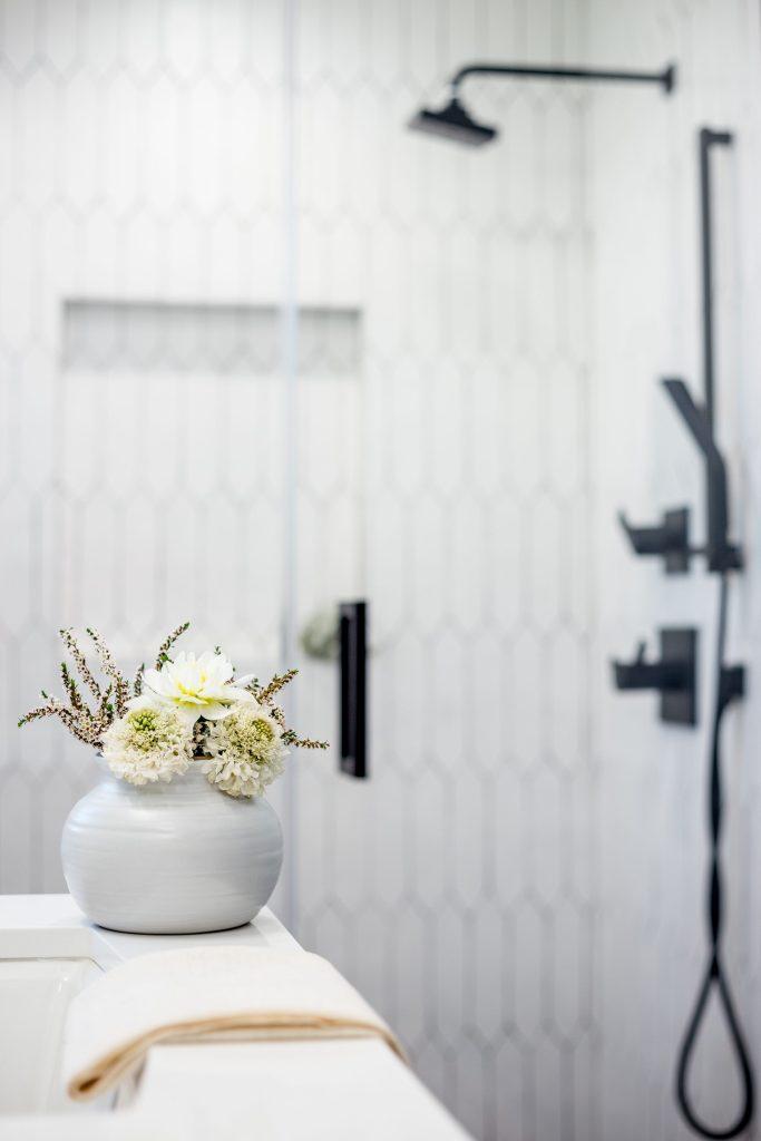 white bathroom black shower trim delta
