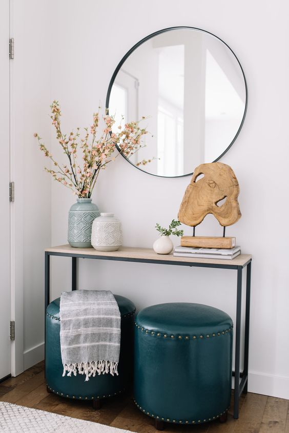 Narrow entry table with blue leather ottomons and wooden driftwood sculpture