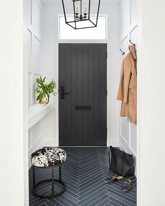High-ceilinged entry with white walls, black herringbone tiles, and cowhide stool
