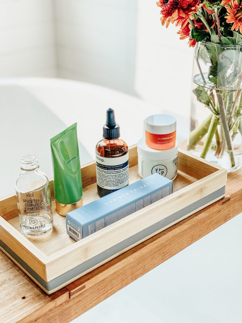 Array of beauty products on a bath tray next to a vase of orange flowers