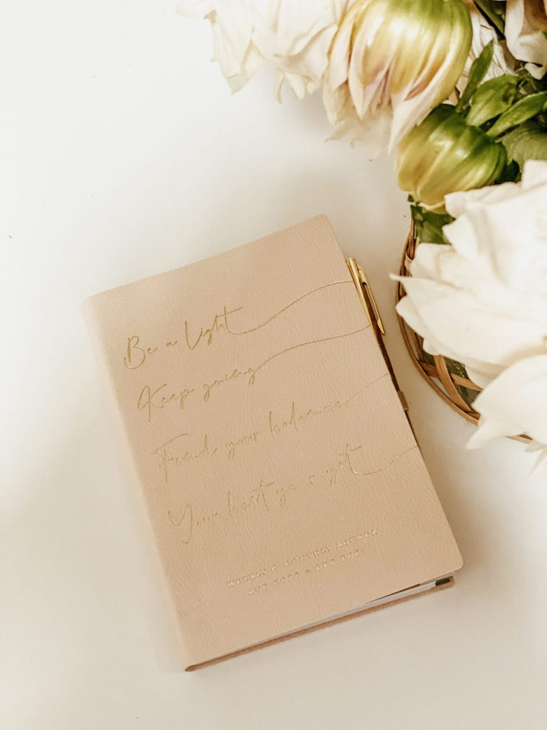 Planner next to flowers on a clean, white desk