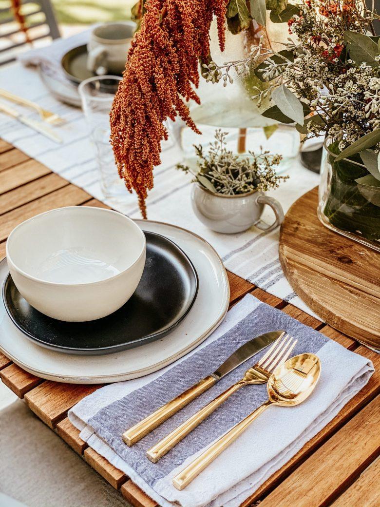 Gold Flatware set next to ceramic table setting