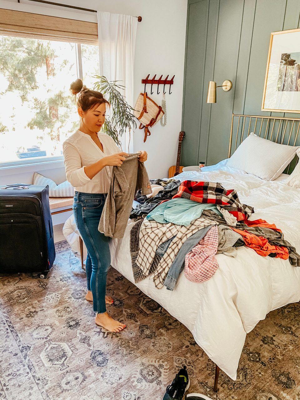 Anita sorts through a pile of clothes in the bedroom