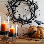 a black wreath of gnarled branches set above orange candles and a pumpkin staged with crow statues