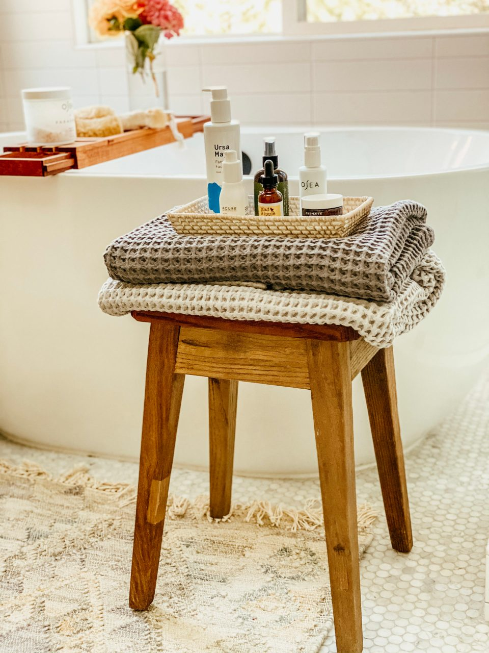 set of skincare products set atop plush waffle towels