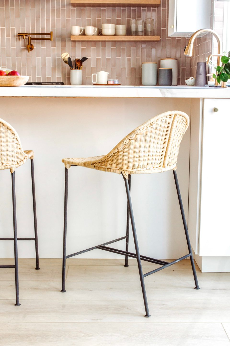 A rattan stool with matte black wire legs pulled up to the new peninsula