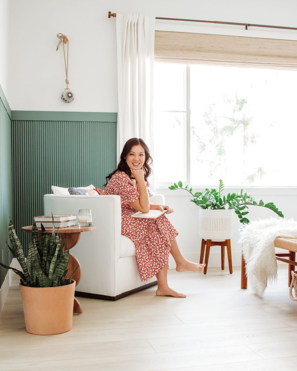 Anita sits in a white upholstered chair against a green paneled wall