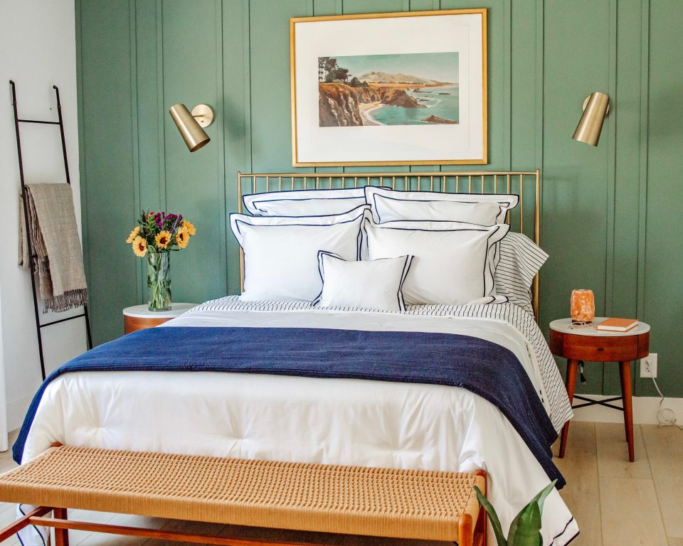 a soft blue and white bed against a relaxing green board and batten