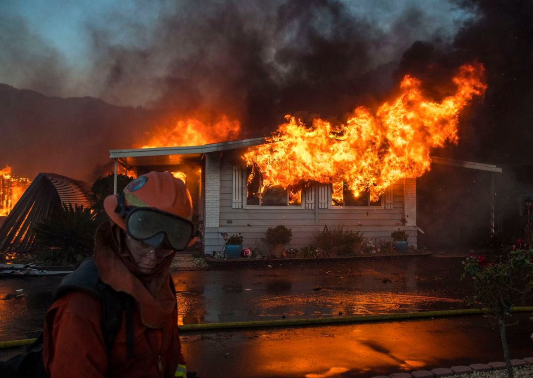 A firefighter turns away from the heat as flames explode through the front windows of a home burning in the Lilac fire.